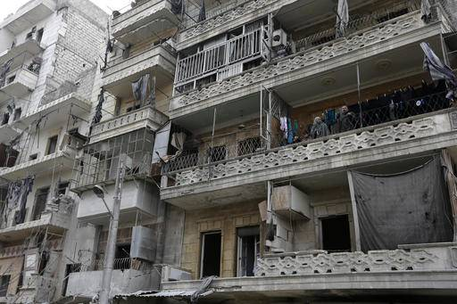 In this picture taken Friday, Jan. 20, 2017 Abdul-Hamid Khatib, right, and his wife Hasnaa, second right, and their grandchildren look down from their apartment balcony in the once rebel-held Ansari neighborhood in the eastern Aleppo, Syria. The street looks as if it was hit by an earthquake and the bombed out building in a former rebel-held northeastern neighborhood of Aleppo is deserted except for the second floor apartment where Khatib and his family are staying. (AP Photo/Hassan Ammar)