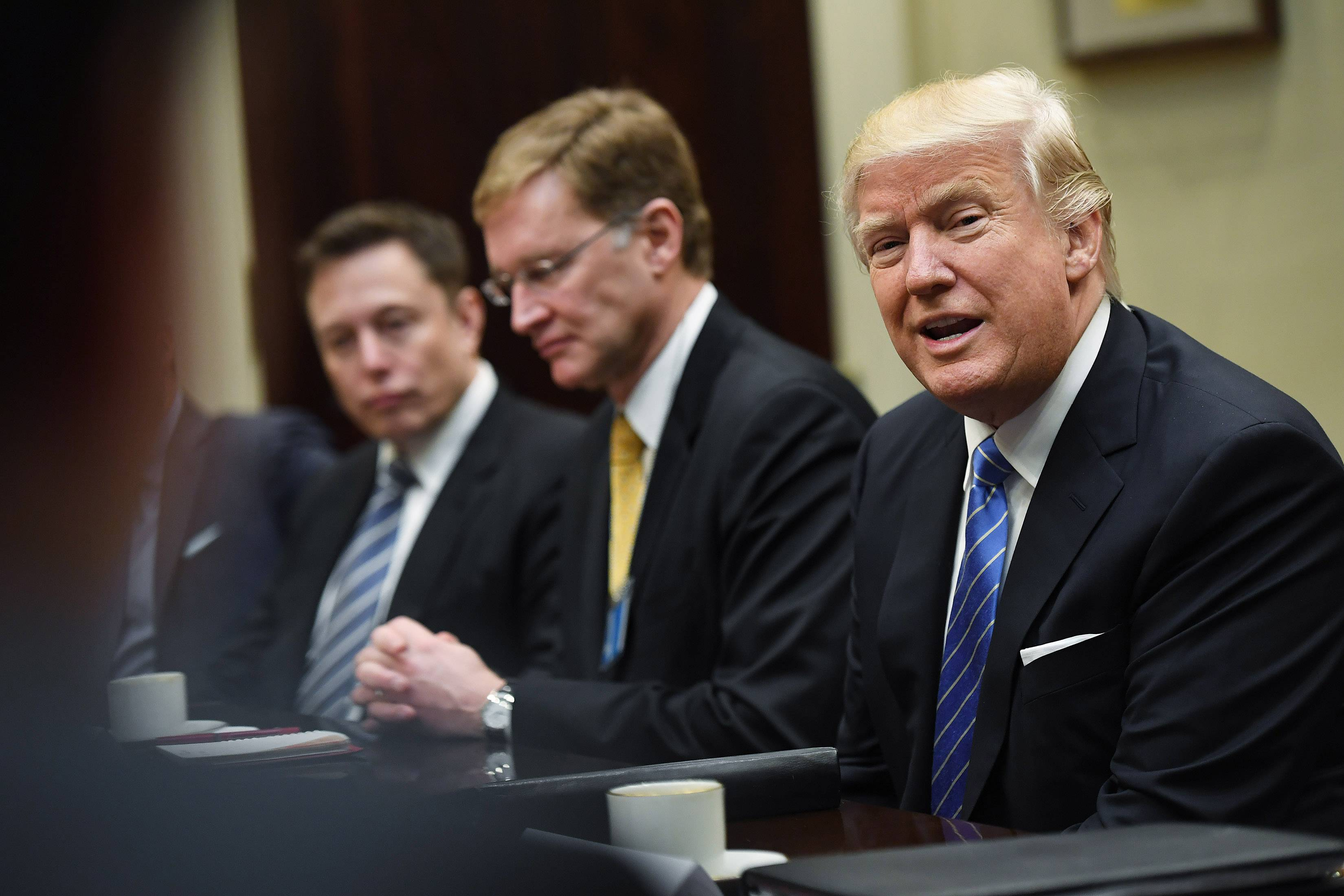 Elon Musk, left, and Wendell Weeks, center, listen to President Donald Trump Monday as he meets with business leaders at the White House on Monday.