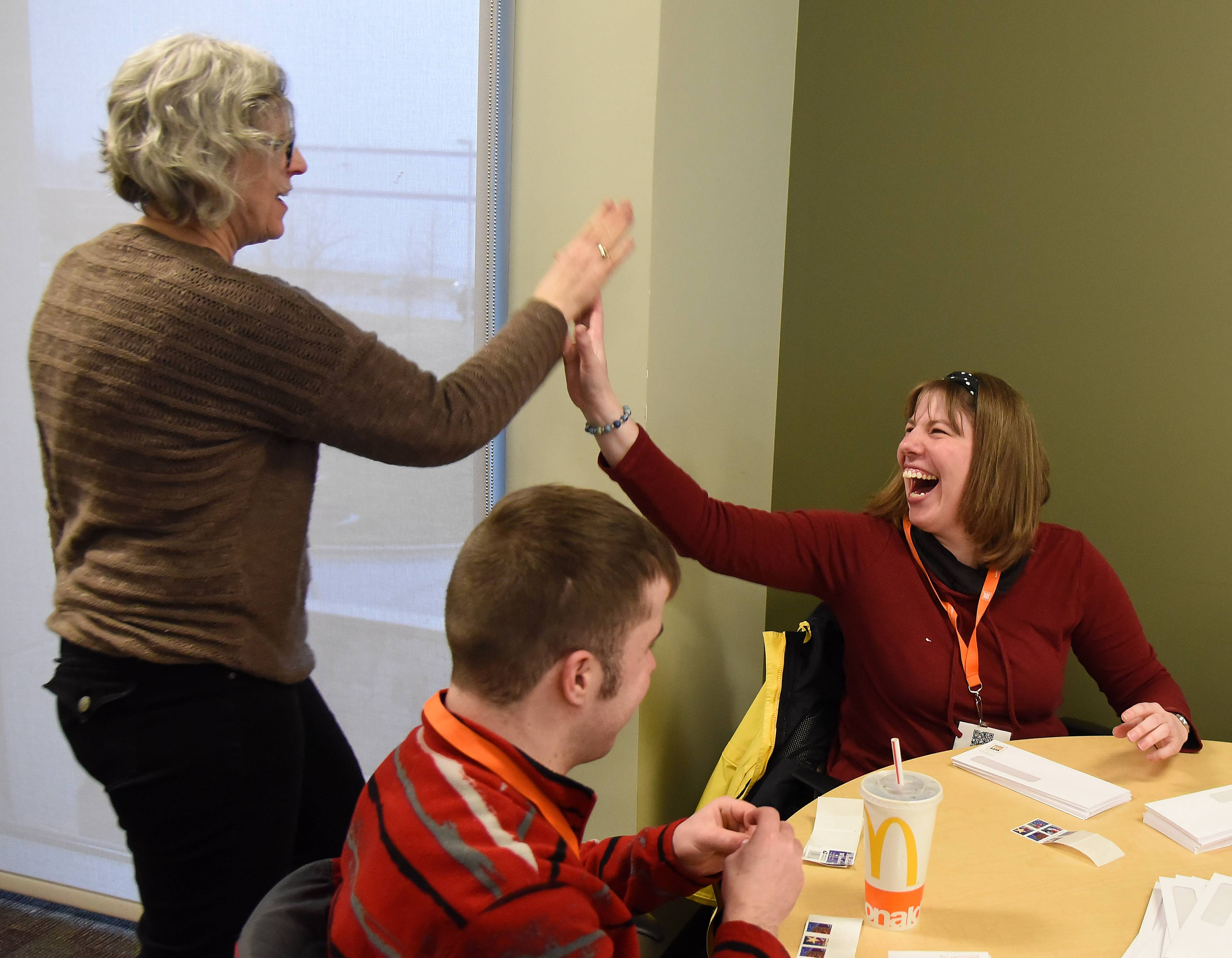 Joy Meade, left, high-fives Michelle Thompson, a Joshua Tree Community volunteer, at the Northern Illinois Food Bank in Geneva on Jan. 16. Meade is donor services coordinator at NIFB.