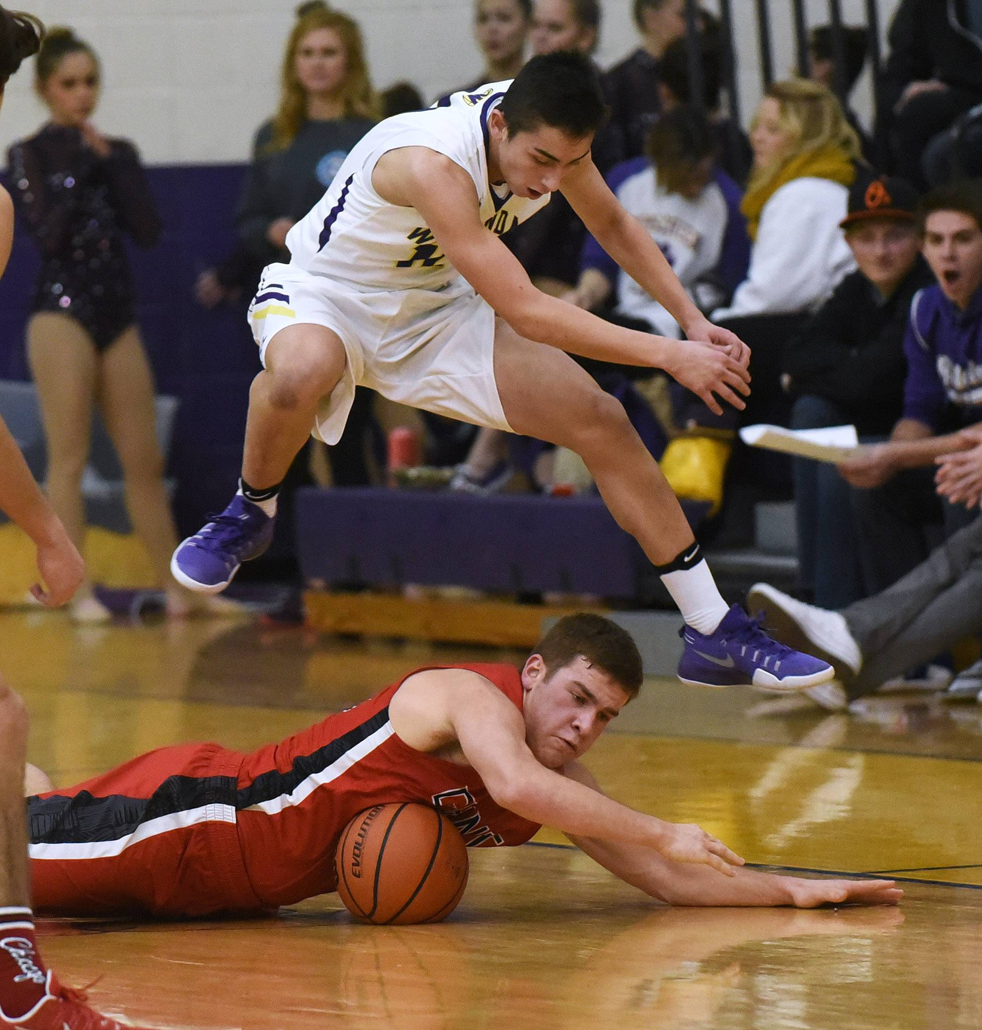 Wauconda's Connor Brannick hops over Grant's Ben Kusiak as they race to a loose ball during Tuesday's game in Wauconda.