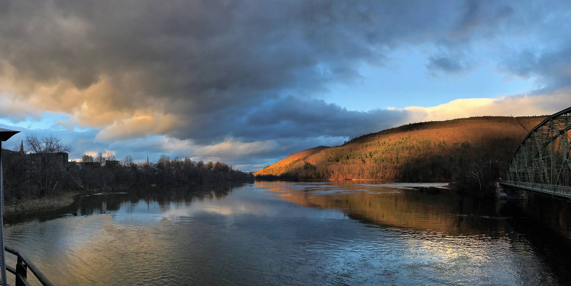 The photo of the Connecticut river separating New Hampshire (on the right) and Vermont (on the left) was taken with an iPhone 7. The most fascinating part of this photo is how the peace and serenity of the sun and calm part of the river meet the turmoil of the clouds and rushing waters of the same sky and river.