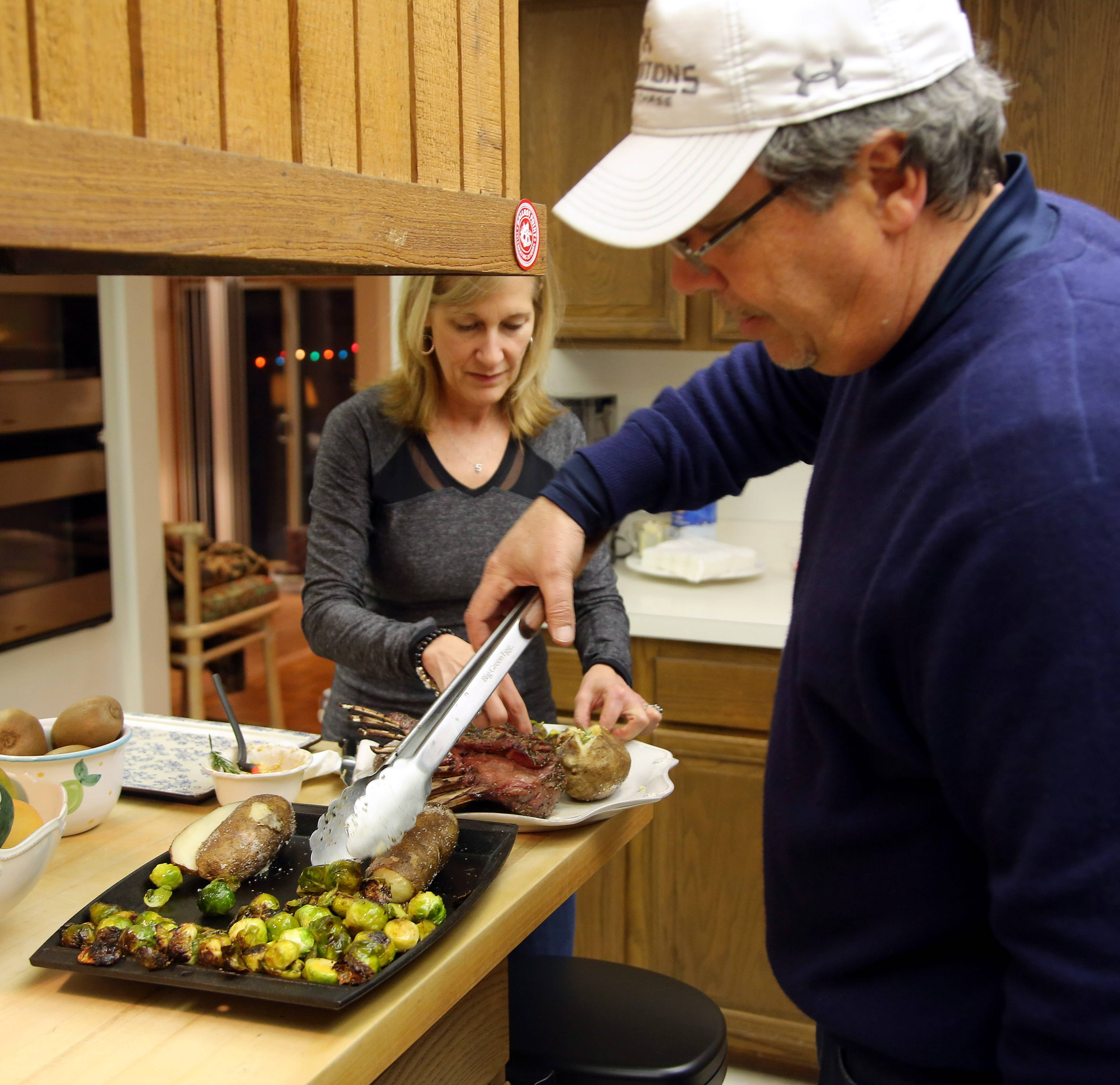 Cooks of the Week of John Harty, right, and Sue Ascher of Riverwoods plate rack of lamb with roasted Brussels sprouts and baked potato. They use their kitchen for prep work but all the food is cooked outdoors.