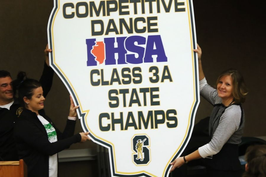Coach Kristin Plekarski, left, and Athletic Director Trish Betthauser hold up the state board that will be displayed in the gym, during a special ceremony Tuesday at Stevenson High School for the varsity Patriettes. The dance team won the IHSA Class 3A Competitive Dance state championship on Saturday.