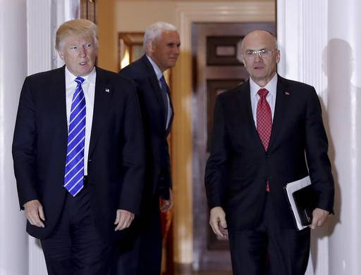 FILE - In this Nov. 19, 2016 file photo, President-elect Donald Trump walks Labor Secretary-designate Andy Puzder from Trump National Golf Club Bedminster clubhouse in Bedminster, N.J. Puzder was CEO of a fast food empire that is outsourcing jobs on his watch, a stark contrast with his boss' threats and tweeted slaps at companies that outsource jobs.