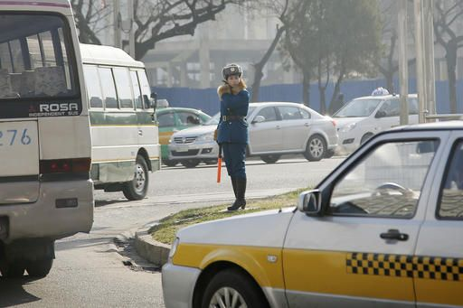 FILE - In this Dec. 1, 2015, file photo, a North Korean traffic police officer directs vehicles in Pyongyang, North Korea. The streets of Pyongyang are more crowded than ever, but Pyonghwa Motors, North Korea's only passenger car company, whose sole factory was designed to produce as many as 10,000 cars a year, appears to be stuck in neutral.