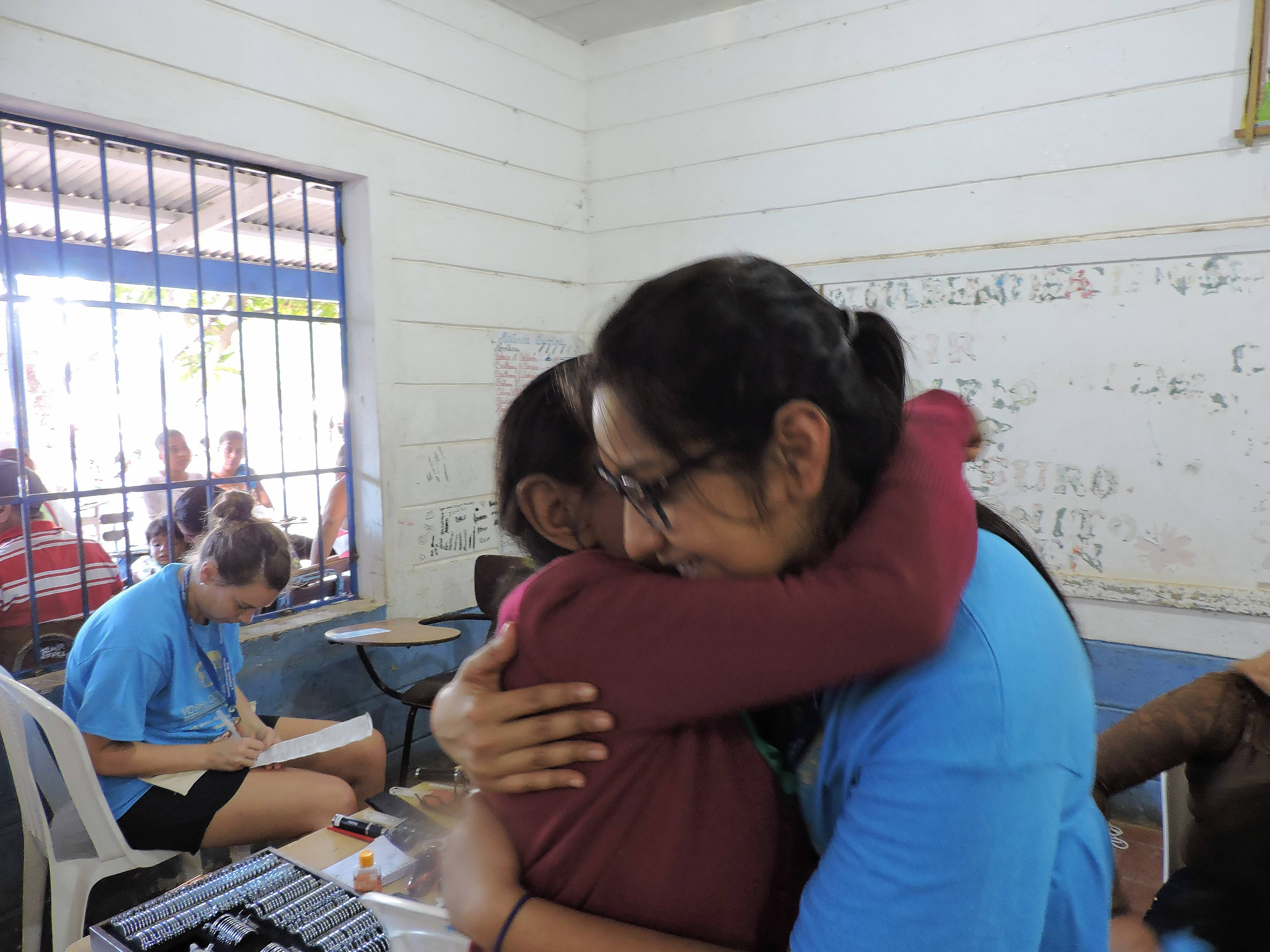An elderly woman hugs one of the interns after receiving glasses that helped restore her vision at eye clinics set up inside the school in San Juan Del Sur, Nicaragua.