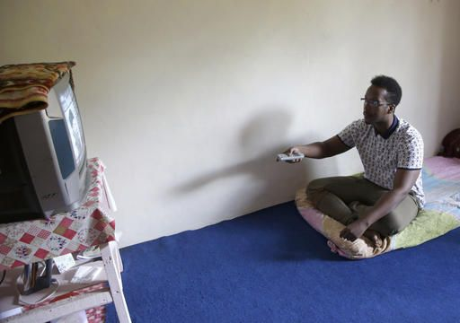 In this Tuesday, Jan. 31, 2017 photo, Mohamed Dahir Saeed, an asylum seeker from Somalia watches TV in his room at a temporary home in puncak, West Java, Indonesia. For thousands of asylum seekers and refugees from Iraq, Somalia and other conflict scarred countries, Indonesia is an often years long hiatus in their lives as they wait for the U.S. or another country to accept them. President Donald Trump's travel ban on seven Muslim countries and suspension of the U.S. refugee program has now made their tenuous situation even more uncertain.