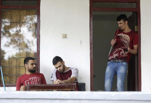 CAPTION ADDITION: CLARIFIES BROTHER AND FRIEND: In this Tuesday, Jan. 31, 2017, photo, Iraqi asylum seeker Ayman, right, chats with his brother, left, and friend, center, during an interview with The Associated Press at ta emporary home in Puncak, West Java, Indonesia. For thousands of asylum seekers and refugees from Iraq, Somalia and other conflict scarred countries, Indonesia is an often years long hiatus in their lives as they wait for the U.S. or another country to accept them. President Donald Trump's travel ban on seven Muslim countries and suspension of the U.S. refugee program has now made their tenuous situation even more uncertain.