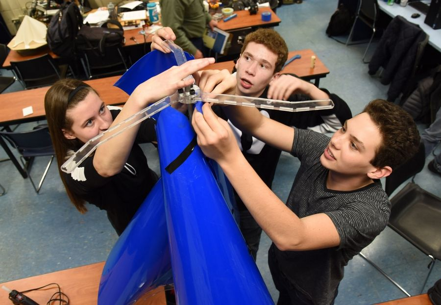 From left, Streamwood High School senior Andrea Greter and juniors Sam Enno and Adam Bender secure the blades of a wind turbine to their brackets as they build a microgenerator that could generate enough electricity to power a safety light for public spaces.