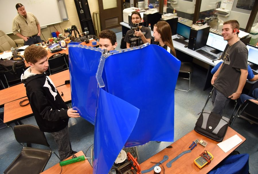 Instructor Matt Erbach watches Streamwood High School students Sam Enno, left, Adam Bender, Andrea Greter, and Joe Nigliaccio as Matthew Suleiman films them building their wind-powered microgenerator -- an idea that could earn them up to $200,000 from a national contest.