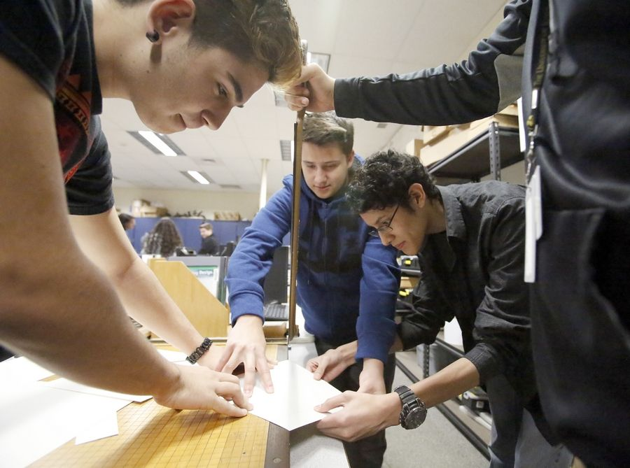 From left, Streamwood High School students Gersi Minxoli, 16, Calvin Wingerd, 16, and Eduardo Torres, 17, start to cut their initial design of the project to create a wind-powered generator.