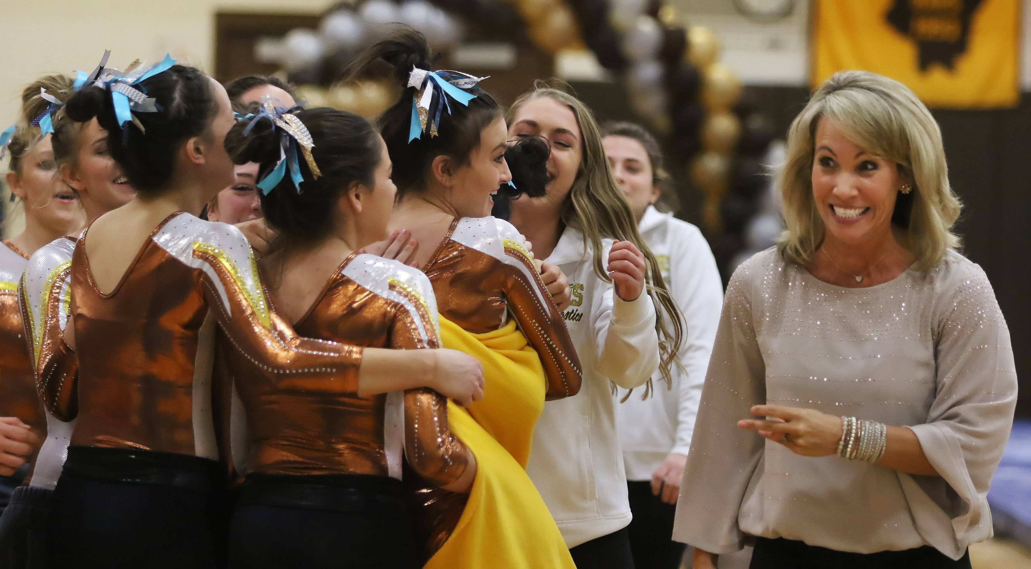 Carmel Catholic assistant girls gymnastics coach Sarah Mikrut Doyle, right, celebrates with her team during the vault competition in Thursday's regional meet hosted by the Corsairs.