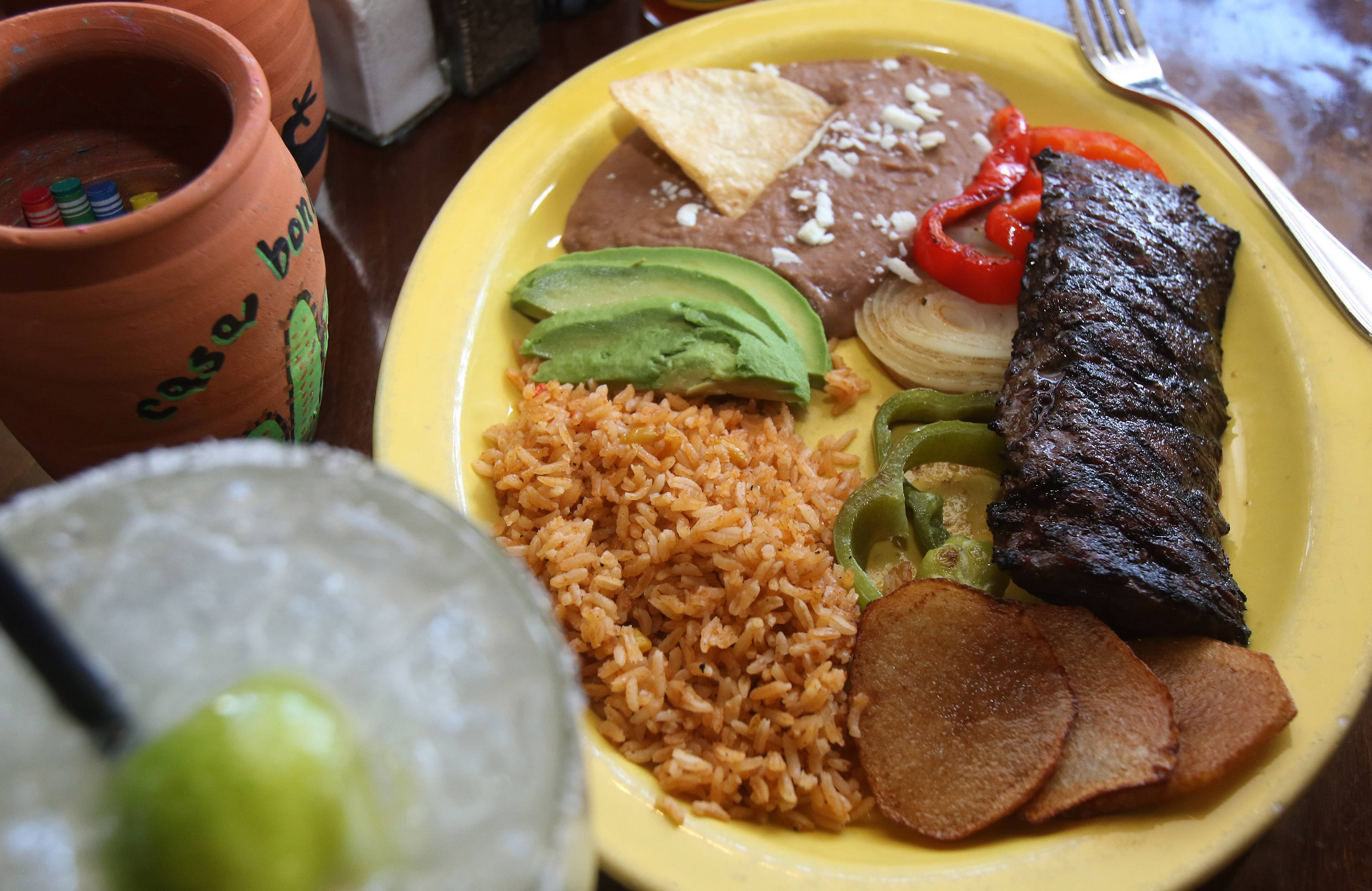 Casa Bonita's carne asada comes with grilled onions, bell peppers, sliced potatoes, beans and rice.
