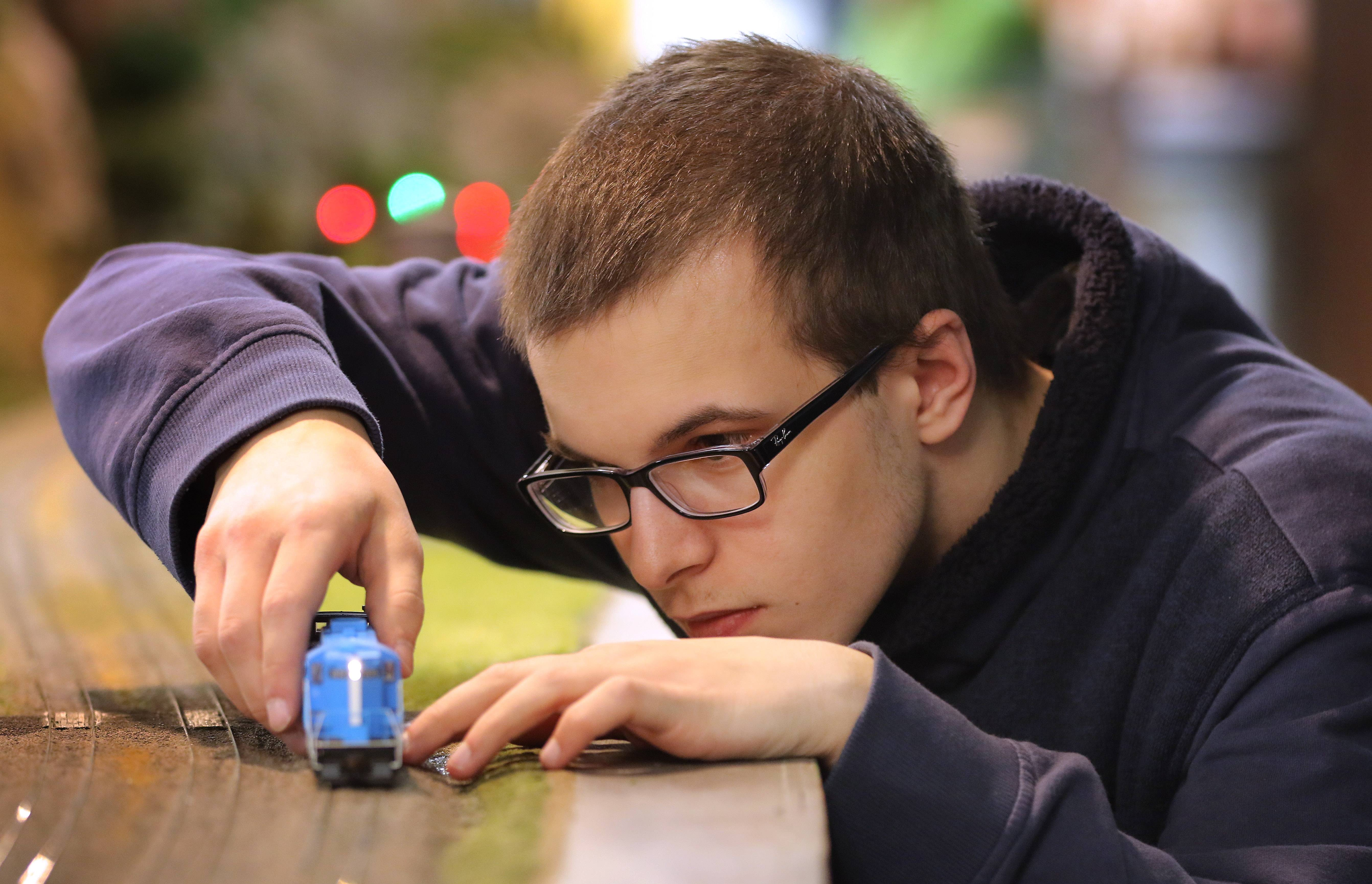 "Kevin Kraszczyk, 16, of Island Lake works with his locomotive at the Lake County Model Railroad Club in Wauconda. ""I got my first Thomas train set and went from Thomas to real trains and ever since then this has been my main hobby and it's been my life,"" he said."