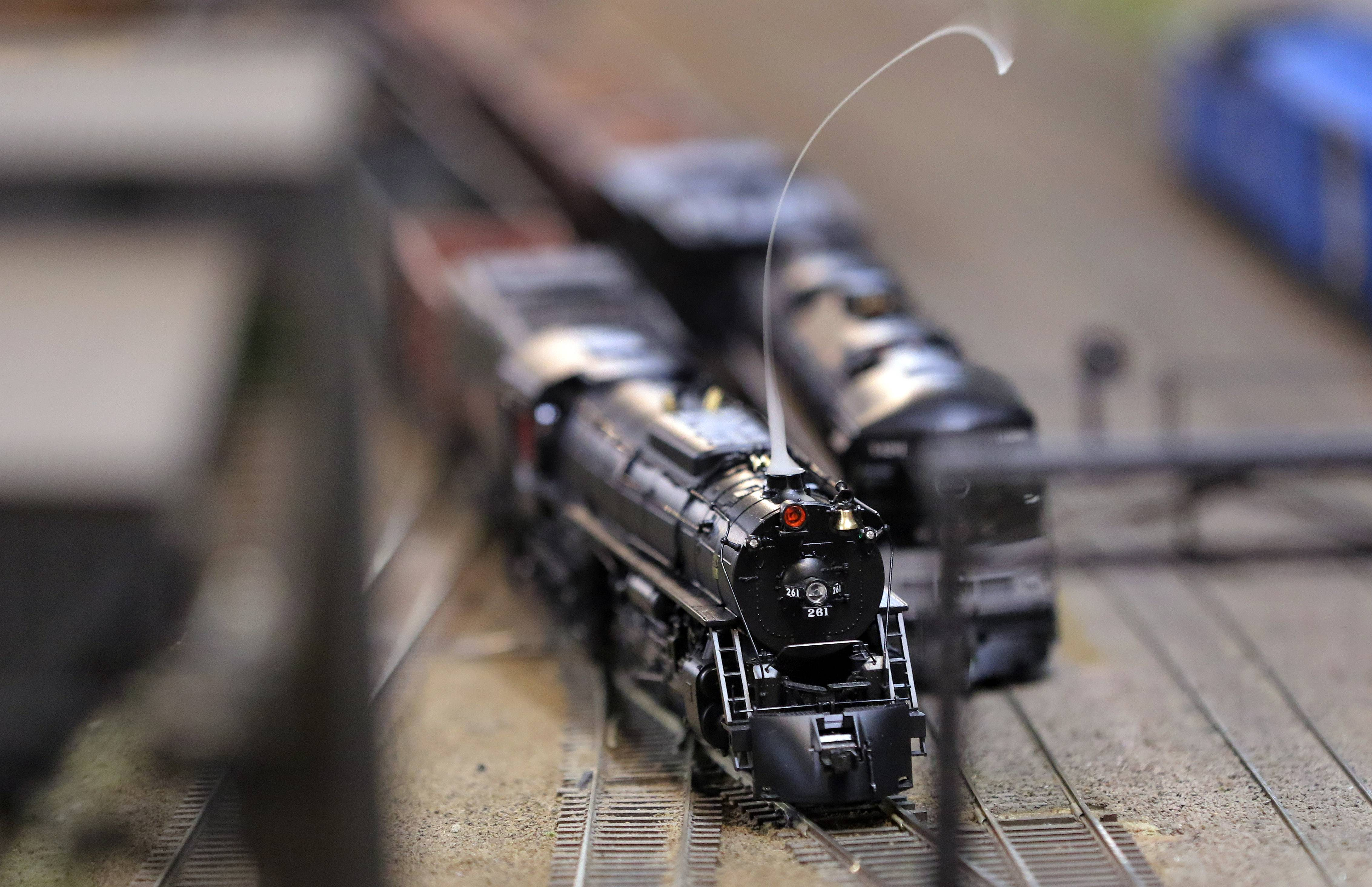 A locomotive spits steam as it chugs down the tracks at the Lake County Model Railroad Club in Wauconda.