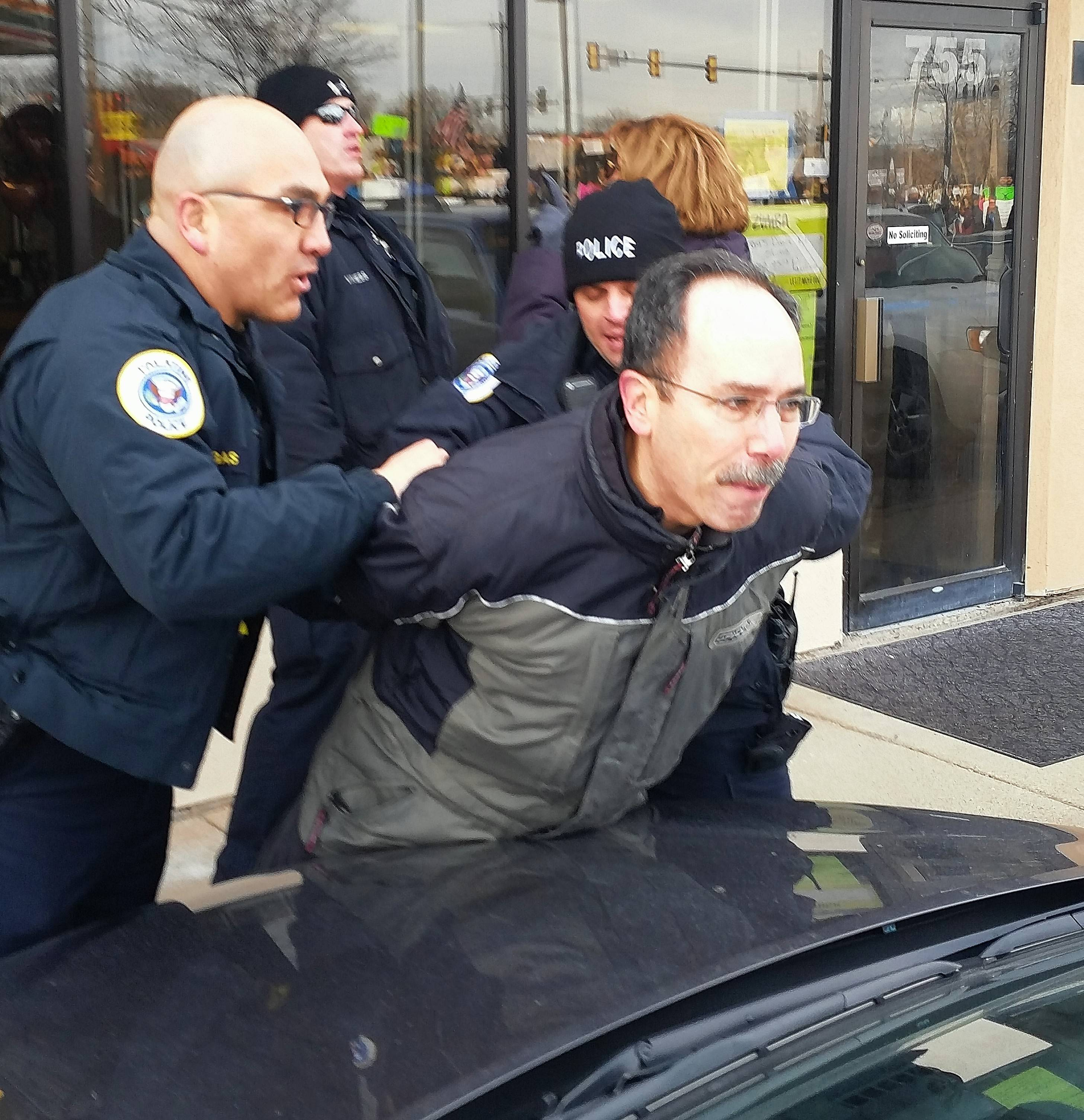 Palatine police arrest a protester Saturday outside the Palatine Township Republican Organization office in Palatine while U.S. Rep. Peter Roskam was inside the office talking to organization members.