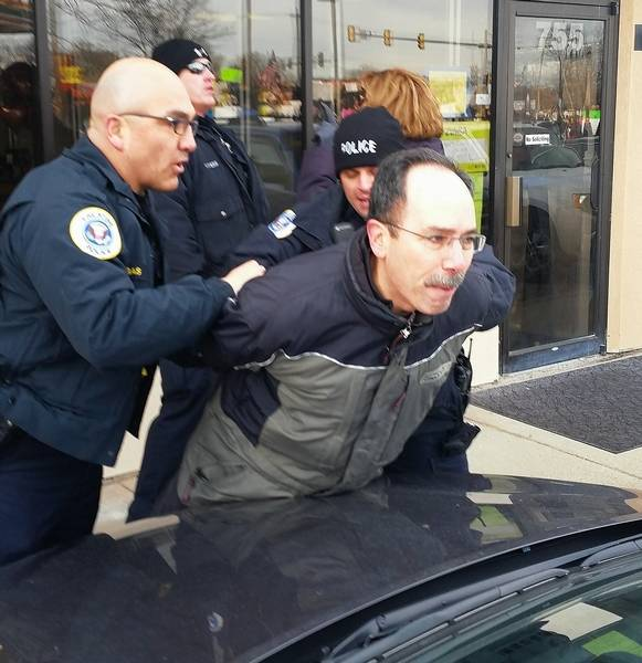 Palatine police arrest Dr. Wynn Sheade as he and about 400 others protested Saturday outside the Palatine Township Republican Organization office in Palatine while U.S. Rep. Peter Roskam was inside talking to organization members.