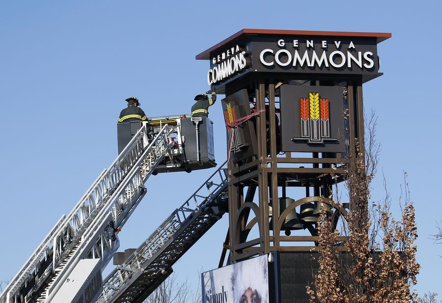Emergency personnel work at the new clock tower in Geneva on Friday. The Kane County coroner said Monday that the worker who was pinned by a lifting device while installing a sign at the clock tower died of asphyxia from a mechanical compression of the neck.