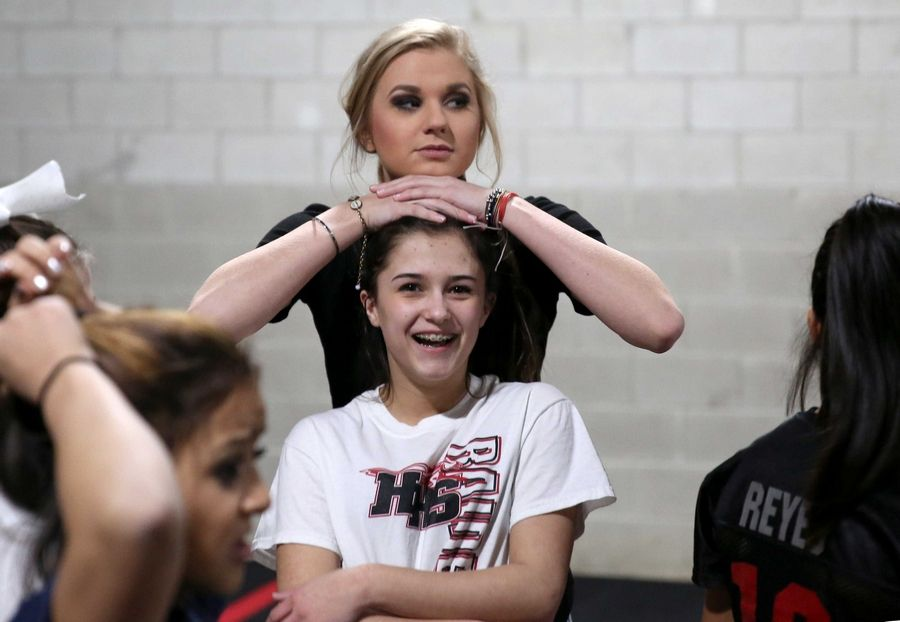 Julia Peluso works with Jessica Raff, 13, of Huntley, one of the students she coaches in a competitive cheer class at Huntley Cheer Association.