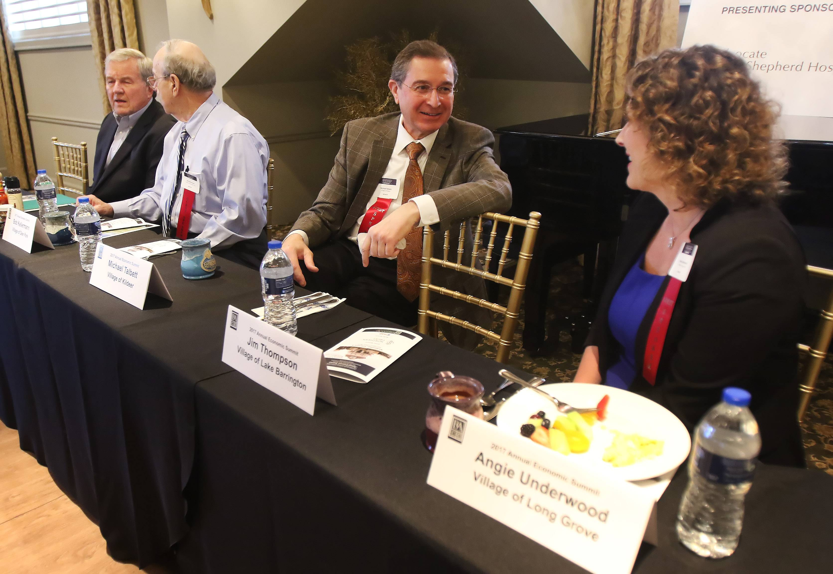 Long Grove Village President Angie Underwood, right, talks to Kildeer Village Administrator Michael Talbett with Deer Park Village President Bob Kellerman and Barrington Hills representative Dan Wolfgram to the left during the 2017 Annual Economic Summit by the Barrington Area Chamber of Commerce at Barrington's White House on Wednesday.