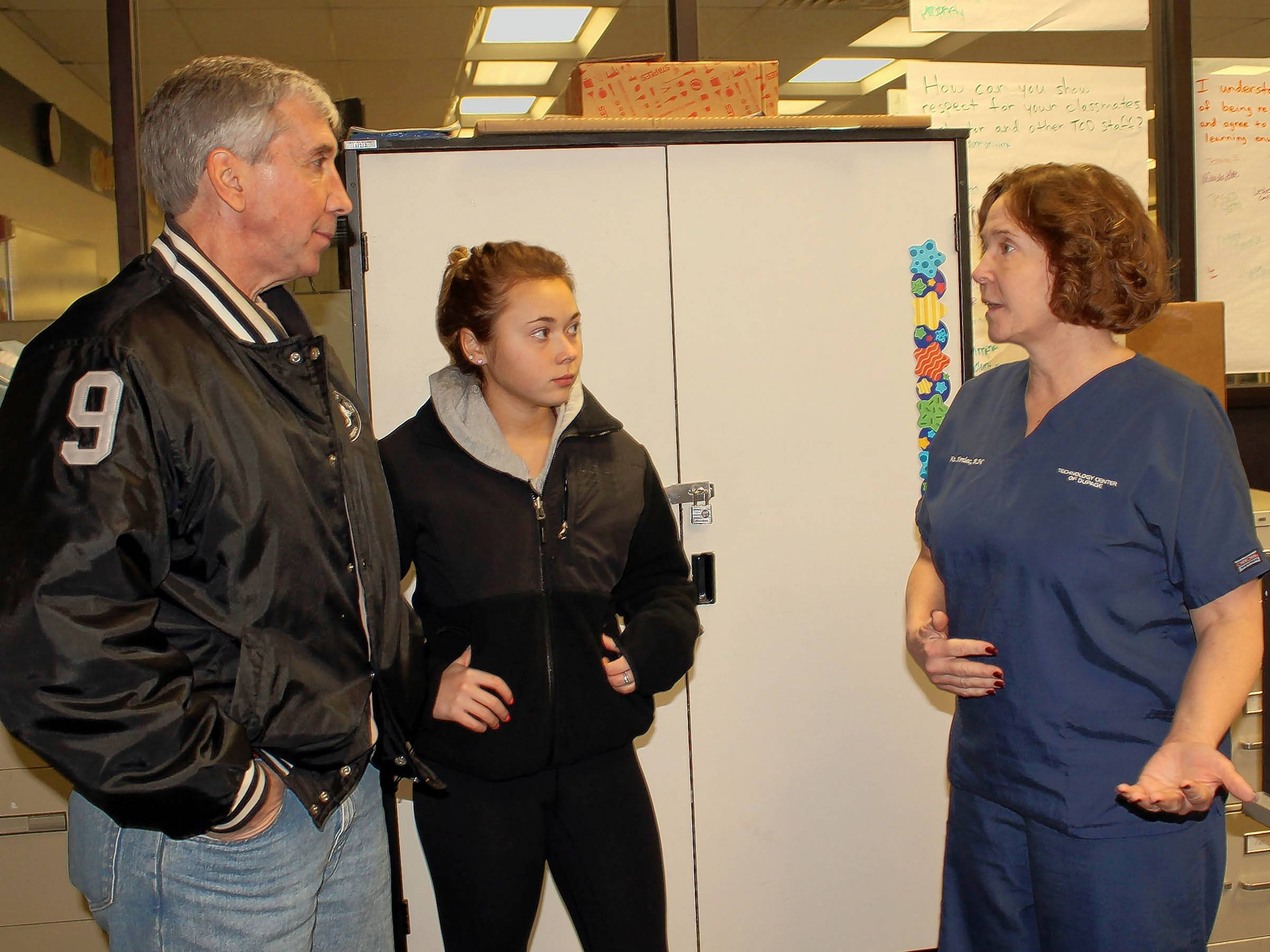 Skip Perillo, left, a 1979 TCD alumnus, accompanied his daughter Jennifer on a recent visit to Technology Center of DuPage to check out the Healthcare Foundations program. They met Marie Kmiec, right, a registered nurse and TCD instructor. Jennifer, a junior at Lake Park High School, plans to enroll in the elective program during her senior year, making her a second generation TCD student.