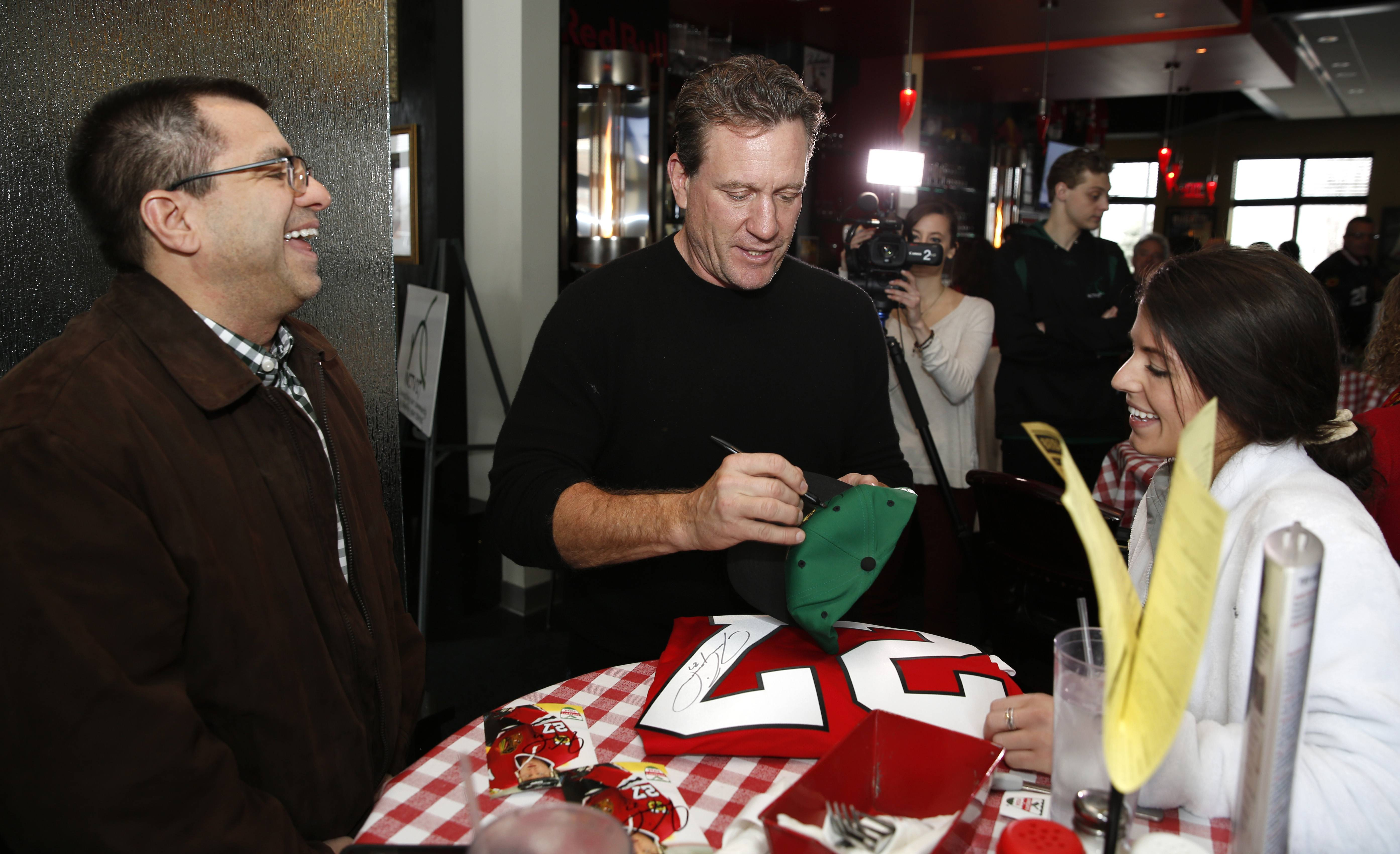 Former Chicago Blackhawks player Jeremy Roenick mingles with fans Dan and Kelsey Brosseau this week while signing autographs at Aurelio's Pizza in Naperville. Roenick also appeared as a celebrity bartender at Aurelio's in Geneva.
