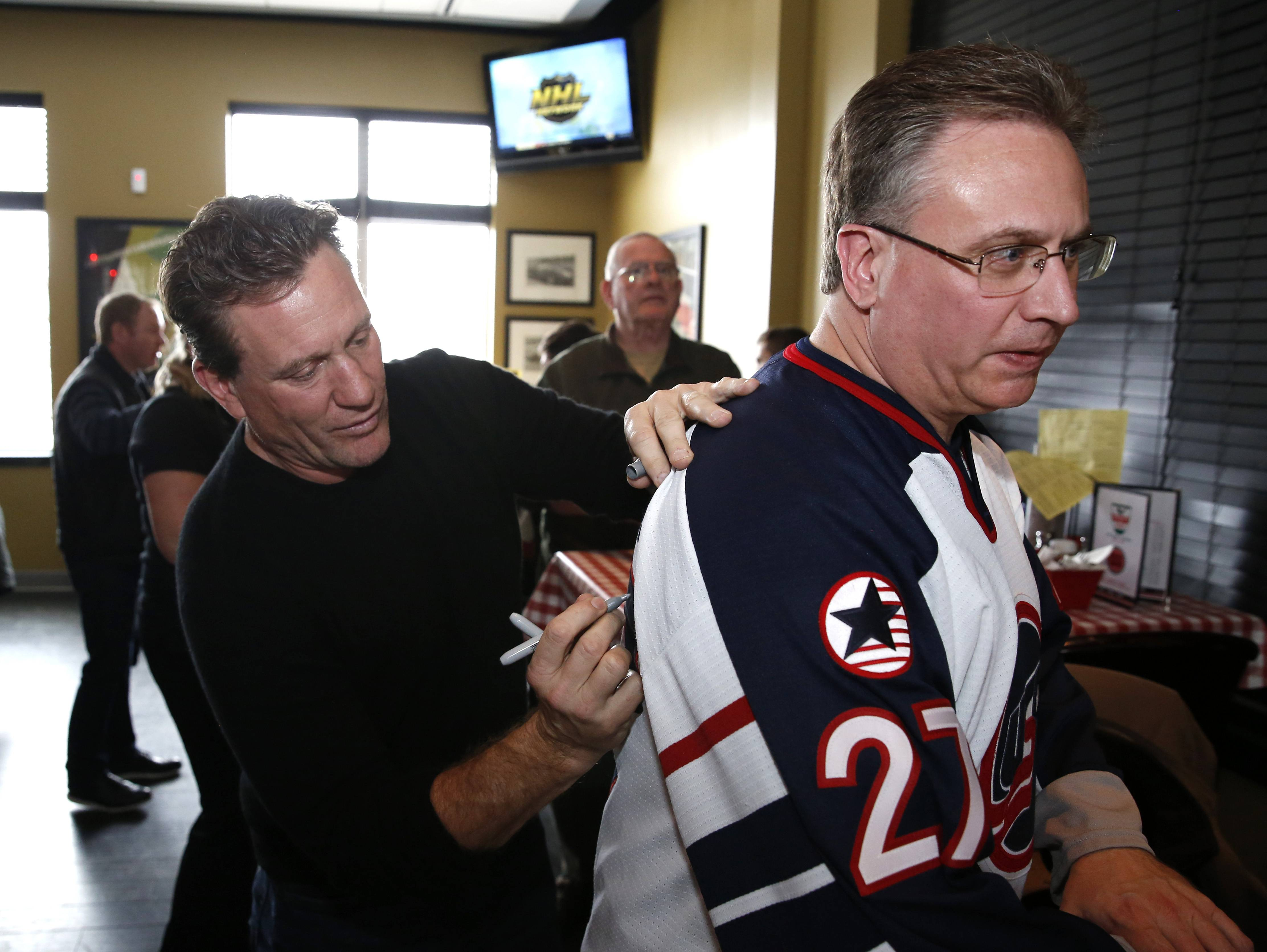 Former Chicago Blackhawks player Jeremy Roenick autographs the back of Naperville resident Chris Gist's Roenick jersey Wednesday at Aurelio's Pizza in Naperville.