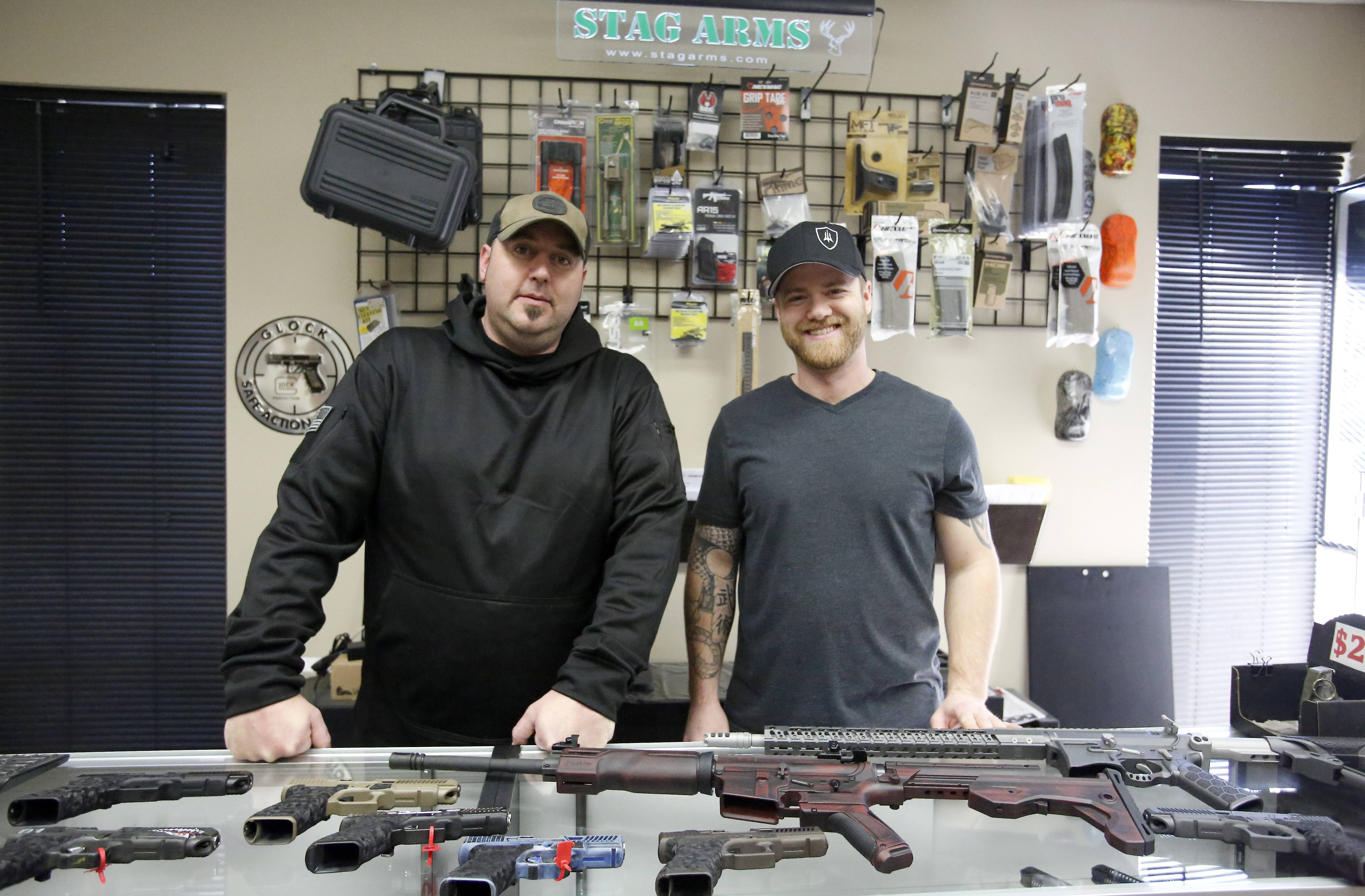 Ty Cobb, left, and Jeremy Rainey, of Trident Defense, display some of the customized firearms they have created. East Dundee recently approved a special-use permit that allows the business to sell its specialized guns on the site.
