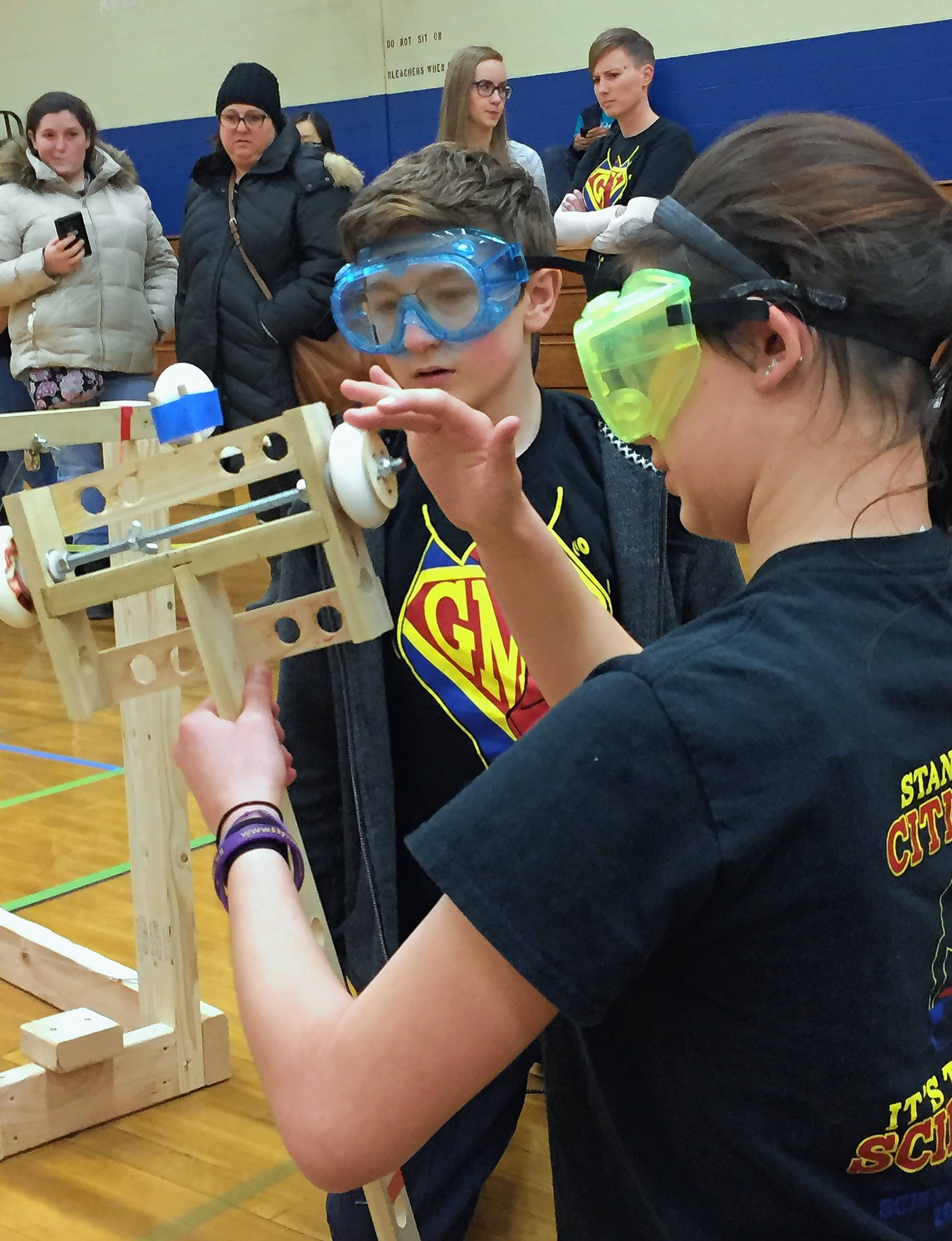 "Alexandria Ries winds the axle of a vehicle as partner Sam Newman watches during ""The Scrambler"" contest at the Grayslake Invitational Science Olympiad Saturday. The two are in seventh grade at Grayslake Middle School."