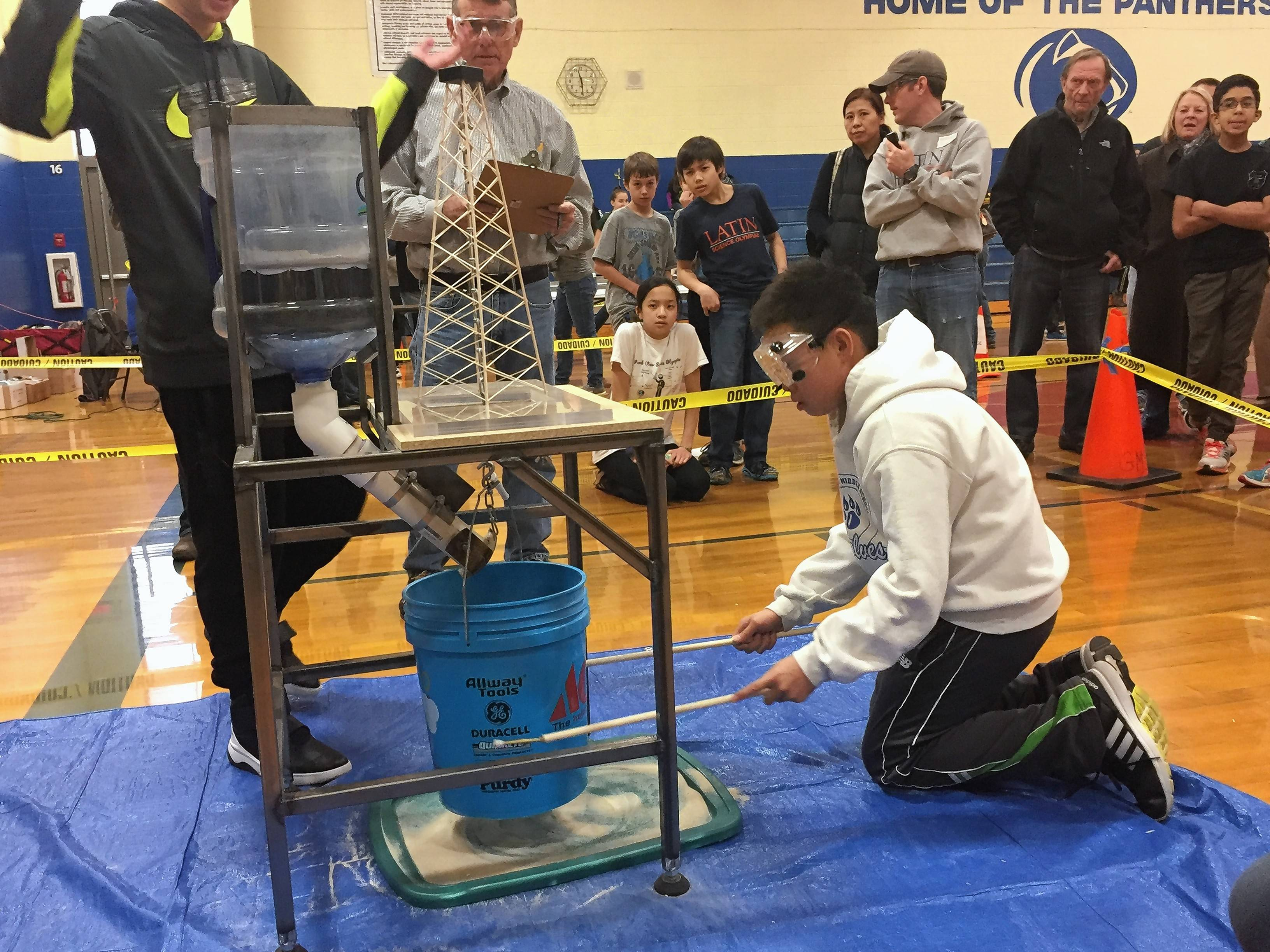 Vincent Lee, a seventh-grader at Woodlawn Middle School, tests how much sand his bridge could bear at the Grayslake Invitational Science Olympiad Saturday.