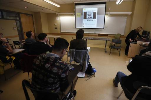 In this Friday, Jan. 20, 2017, photo, students in a journalism course at Kean University in Union, N.J., watch a presentation on fake news. Teachers from elementary school through college have been ramping up media literacy training to recognize bogus reports and understand their potential to weaken civic culture.