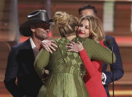 "Tim McGraw, left, and Faith Hill, right, congratulate Adele after presenting her with the award for record of the year for ""Hello"" at the 59th annual Grammy Awards on Sunday, Feb. 12, 2017, in Los Angeles. (Photo by Matt Sayles/Invision/AP)"