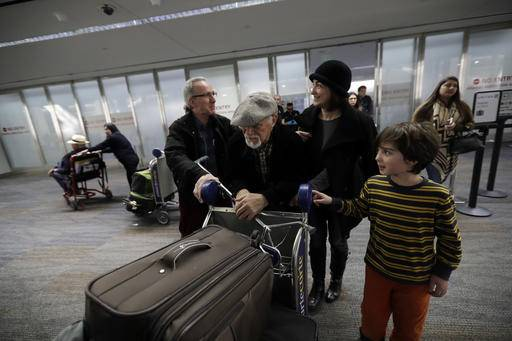 FILE - In this Saturday, Jan. 28, 2017, file photo, Abdollah Mostafavi, center, arriving from Tehran, Iran, is met by his family including son-in-law Nasser Sorkhavi, left, daughter Mozhgan Mostafavi, second from right, and grandson Kourosh Sorkhavi at San Francisco International Airport in San Francisco. Mostafavi was held at the airport for some time as a result of President Donald Trump's executive order. A federal judge has granted a preliminary injunction barring the Trump administration from implementing its travel ban in Virginia. A federal appeals court in California has already upheld a national temporary restraining order stopping the government from implementing the ban. (AP Photo/Marcio Jose Sanchez, File)
