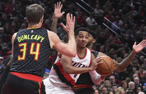 Portland Trail Blazers guard C.J. McCollum passes the ball as he drives to the basket on Atlanta Hawks guard Mike Dunleavy during the first half of an NBA basketball game in Portland, Ore., Monday, Feb 13, 2017. (AP Photo/Steve Dykes)