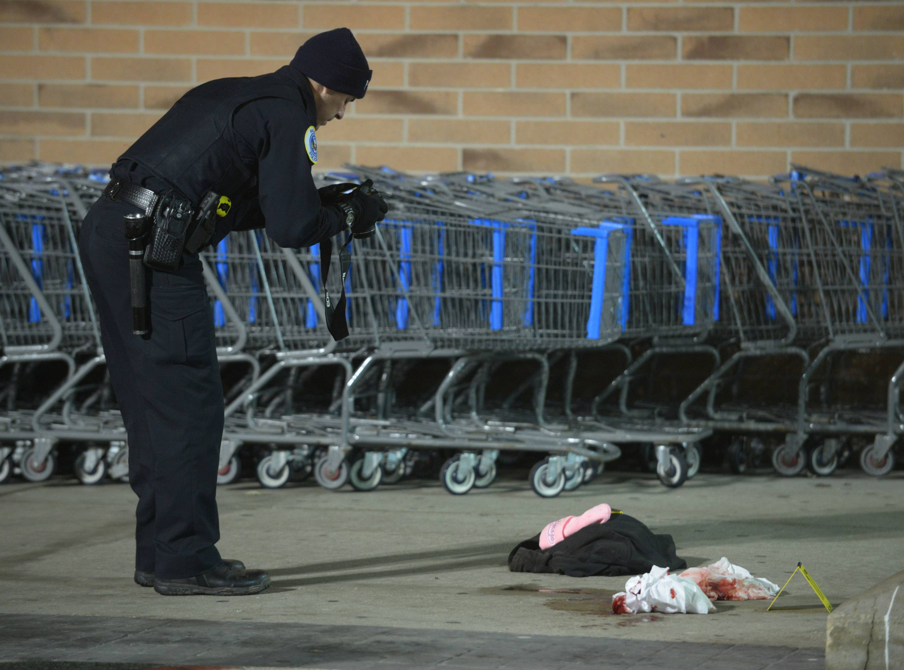 A Palatine police officer photographs crime scene evidence outside a store at 1555 N. Rand Road in Palatine on Feb. 7.
