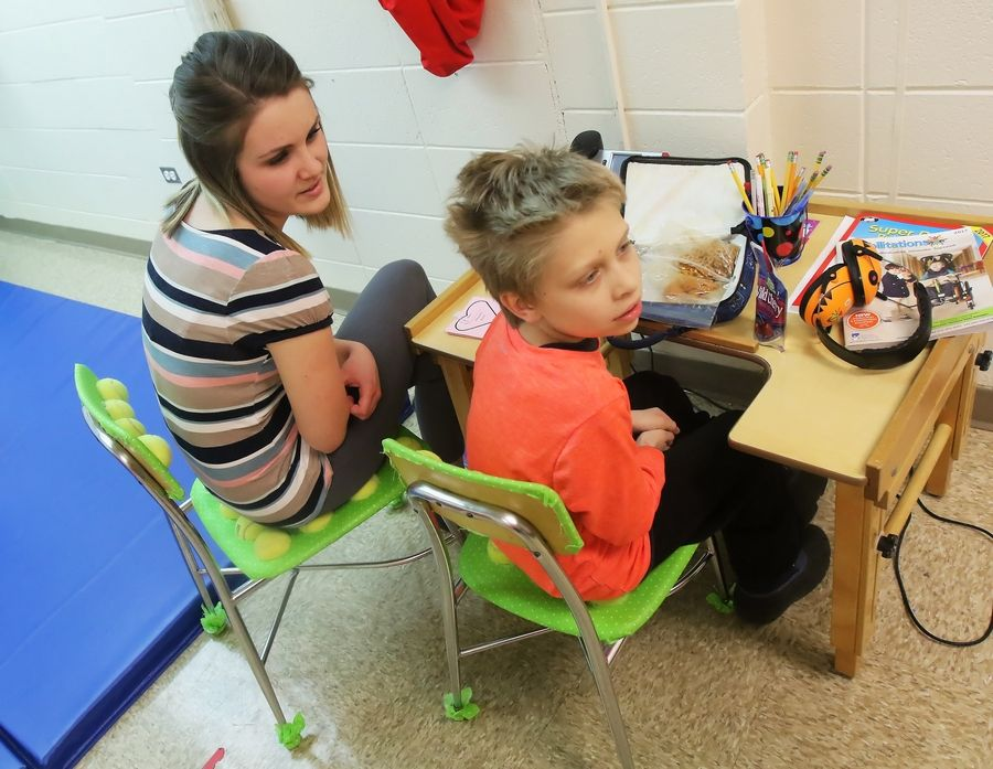 Speech language pathologist Amy Maplethorpe works with Michal Kozupa, 9, of Round Lake Beach as they sit on tennis ball sensory chair she designed and is using at Raymond Ellis Elementary School in Round Lake.