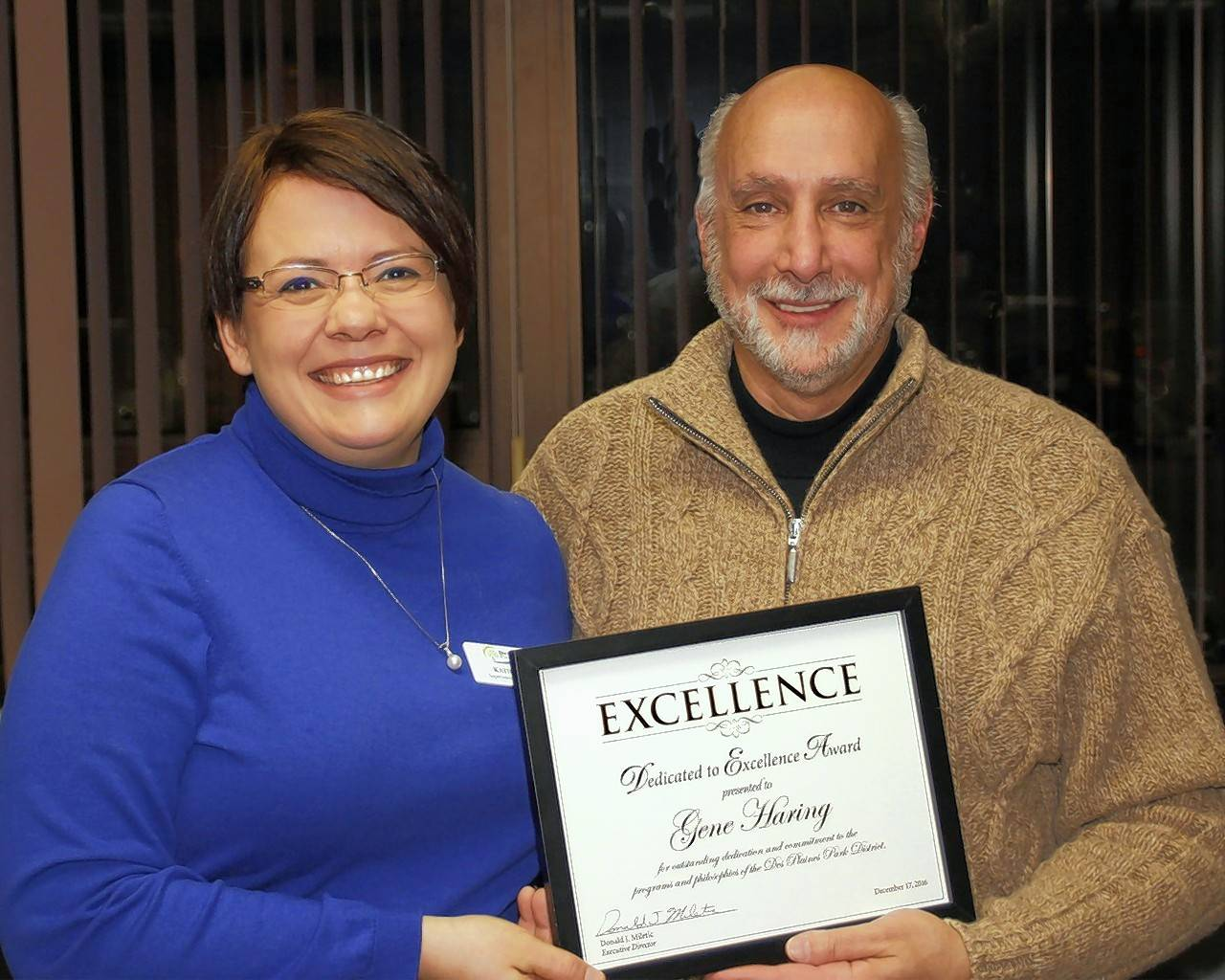 Katie Skibbe, superintendent of business, congratulates Gene Haring on his Dedicated to Excellence Award at the Des Plaines Park District board meeting in December.