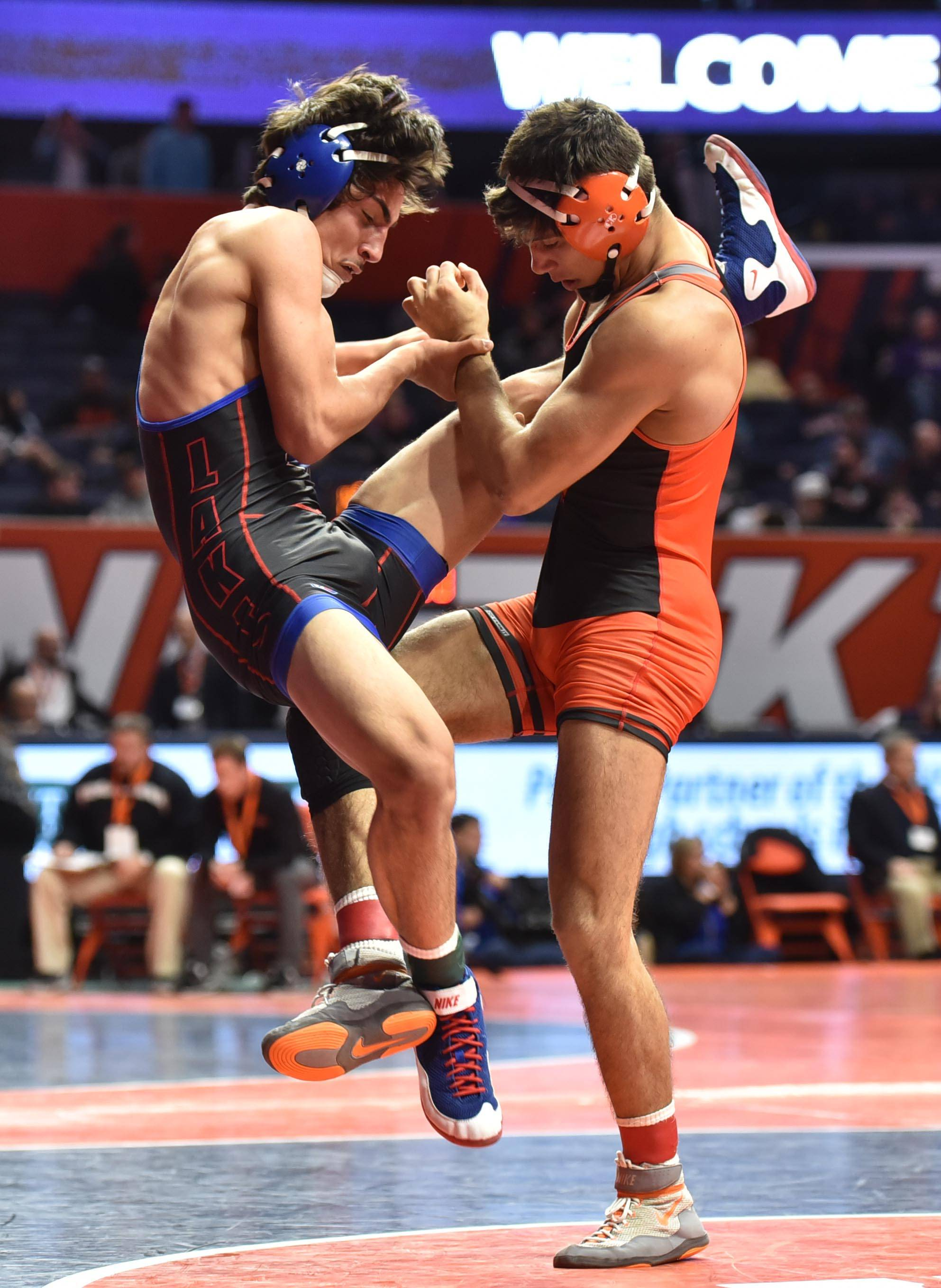 Lakes High School's Xavian Girona is tripped by Washington's Kyle Goin in the Class 2A 152 -pound quarterfinal bout Friday at the IHSA state wrestling tournament preliminaries.