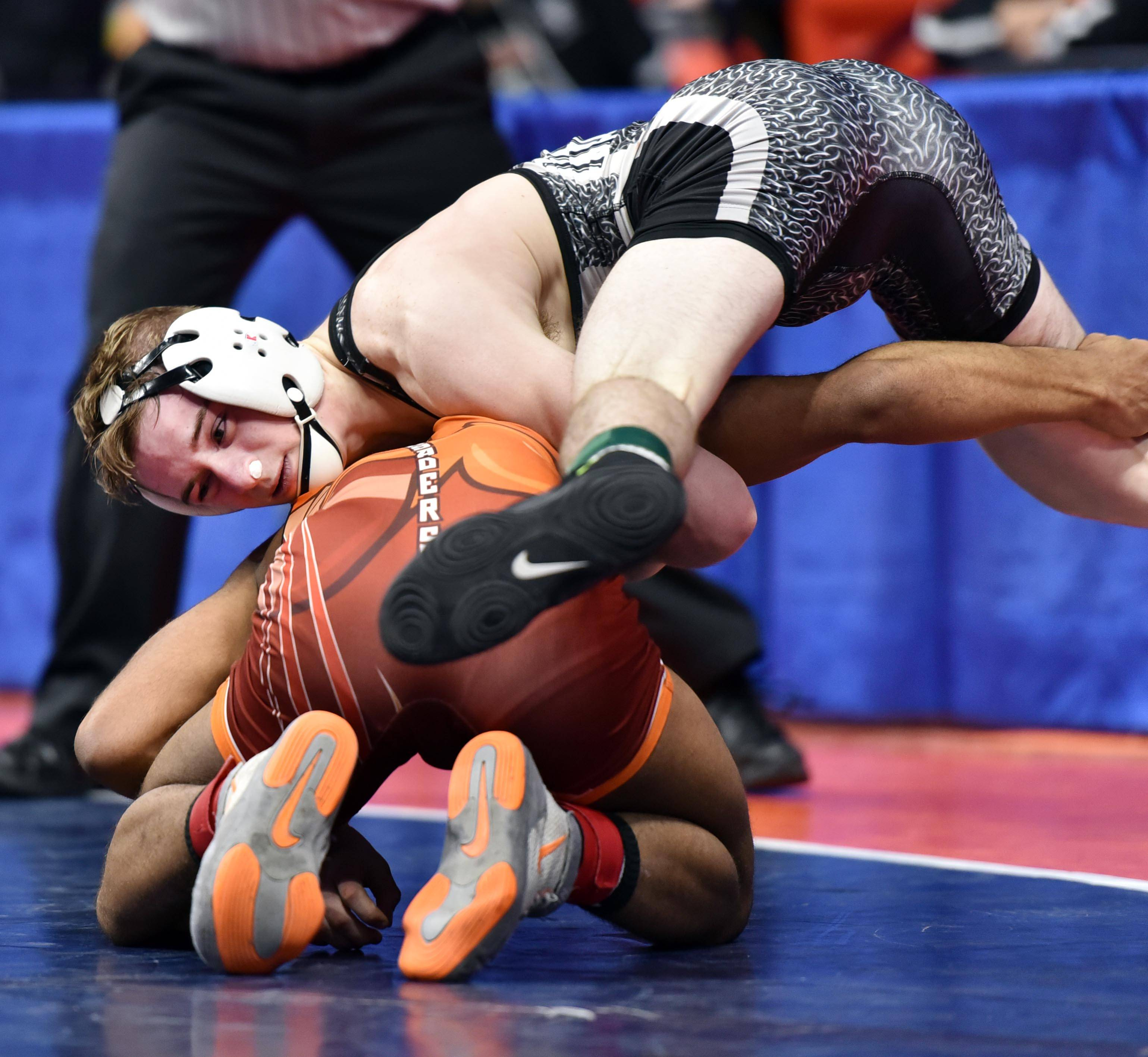 Kaneland's Austin Kenzie competes with Hassan Johnson of Brother Rice in theClass 2A 120-pound quarterfinal bout Friday at the IHSA state wrestling tournament preliminaries.