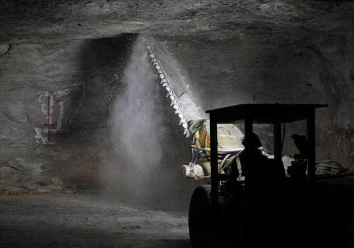 In this Jan. 27, 2017 photo, an American Rock Salt Co. worker operates an undercutter to trim a piece of low-hanging roof at the mine in Hampton Corners, N.Y. Inside the nation's most productive road salt mine, workers in ghostly tunnels are praying for snow. Fiercer winters mean better business, longer hours and fatter paychecks at what's billed as the nation's most productive salt mine, which ships trainloads of snow-melting road salt to municipalities across the Northeast.
