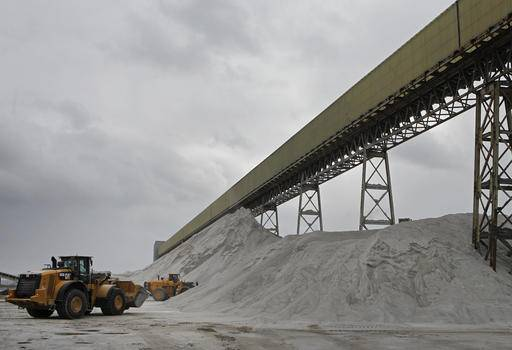 In this Jan. 27, 2017 photo, American Rock Salt Co. loaders work a road salt pile at the mine in Hampton Corners, N.Y. Deep below upstate New York's farm country, workers in ghostly tunnels are praying for snow. Fiercer winters mean better business, longer hours and fatter paychecks at what's billed as the nation's most productive salt mine, which ships trainloads of snow-melting road salt to municipalities across the Northeast.