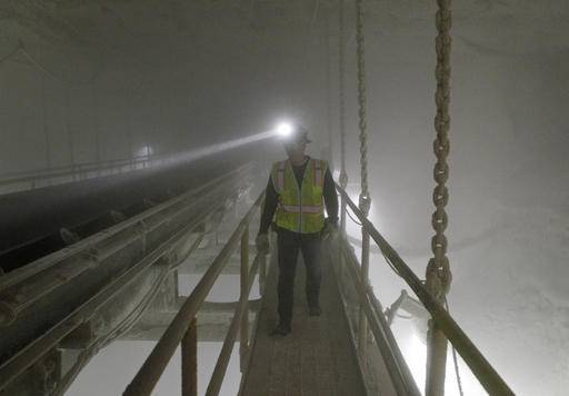 In this Jan. 27, 2017 photo, an American Rock Salt Co. mine production worker inspects the surge bin at the mine in Hampton Corners, N.Y. Deep below upstate New York's farm country, workers in ghostly tunnels are praying for snow. Fiercer winters mean better business, longer hours and fatter paychecks at what's billed as the nation's most productive salt mine, which ships trainloads of snow-melting road salt to municipalities across the Northeast.
