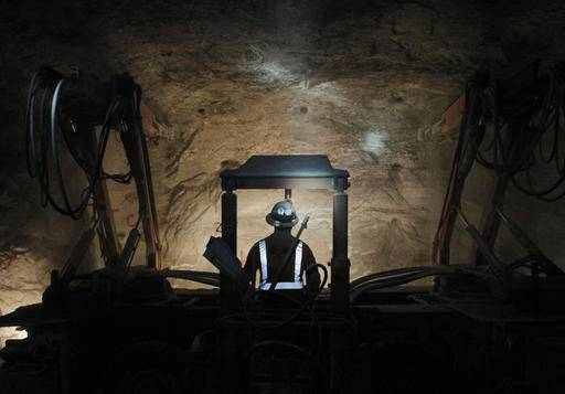 In this Jan. 27, 2017 photo, American Rock Salt Co. worker Bob Jaggard operates a face drill to create blast holes in a wall at the mine in Hampton Corners, N.Y. Deep below upstate New York's farm country, workers in ghostly tunnels are praying for snow. Fiercer winters mean better business, longer hours and fatter paychecks at what's billed as the nation's most productive salt mine, which ships trainloads of snow-melting road salt to municipalities across the Northeast.