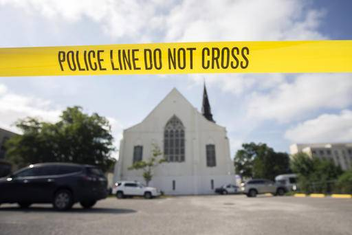 FILE - In this Friday, June 18, 2015 file photo, police tape surrounds the parking lot behind the AME Emanuel Church as FBI forensic experts work the crime scene where nine people where shot by Dylann Storm Roof, 21, in Charleston, S.C. Since the Oklahoma City bombing in 1995, the Southern Poverty Law Center has tracked domestic terrorist plots and attacks in the United States. It lists more than 100, including the slaying of nine black churchgoers during a 2015 prayer meeting in Charleston, S.C.