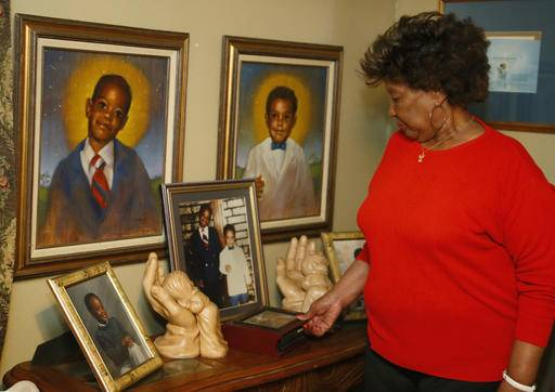 In this Tuesday, Feb. 14, 2017 photo, Jannie Coverdale looks over photos of her two grandsons, Aaron Coverdale, left, and Elijah Coverdale, right, who both died in the 1995 Oklahoma City bombing, in her home in Oklahoma City. Coverdale said she sees a terrorism risk from potential attackers who sneak into the U.S. from abroad.
