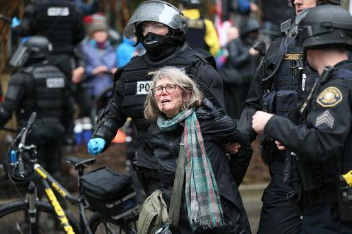 A woman is detained during a protest Monday, Feb. 20, 2017, in Portland, Ore. Thousands of demonstrators turned out Monday across the U.S. to challenge President Donald Trump in a Presidents Day protest dubbed Not My President's Day. (Dave Killen/The Oregonian via AP)