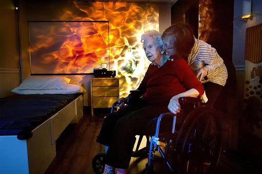 In this Jan. 19, 2017 photo, Rebecca Perkins, right, brings her mother, Catherine  Whitaker, into the sensory room in the Meadows Mennonite Retirement Community in Meadows, Ill. The room includes projected light effects, a musical water bed and a host of textured wall pieces and other features designed to help residents with Alzheimer's disease and other types of dementia hold onto reality. (David Proeber/The Pantagraph via AP)