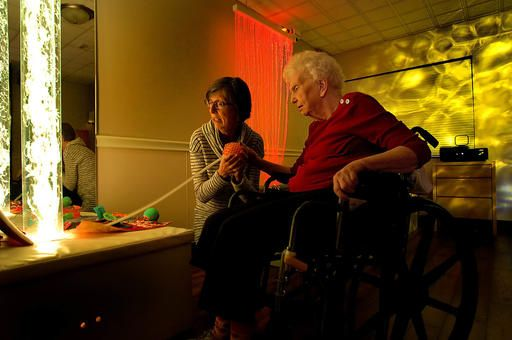 In this Jan. 19, 2017 photo, Rebecca Perkins, left, shares a tactile ball with her  mother, Catherine Whitaker, in the sensory room in the Meadows Mennonite Retirement Community in Meadows, Ill. The room includes projected light effects, a musical water bed and a host of textured wall pieces and other features designed to help residents with Alzheimer's disease and other types of dementia hold onto reality. (David Proeber/The Pantagraph via AP)