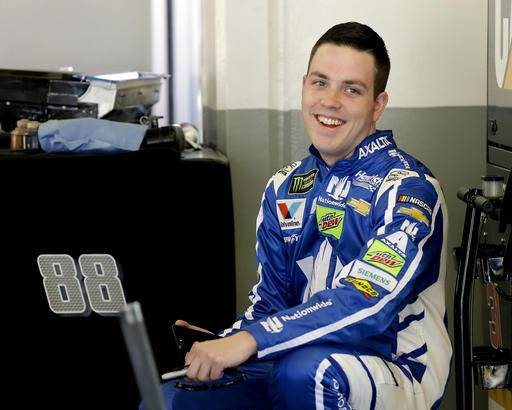 Alex Bowman smiles to team members in his garage during a practice session for the Clash NASCAR auto race at Daytona International Speedway, Friday, Feb. 17, 2017, in Daytona Beach, Fla. (AP Photo/Terry Renna)