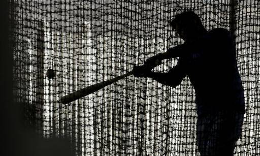 An unidentified Kansas City Royals player practices in a batting cage during spring training baseball practice Thursday, Feb. 16, 2017, in Surprise, Ariz. (AP Photo/Charlie Riedel)